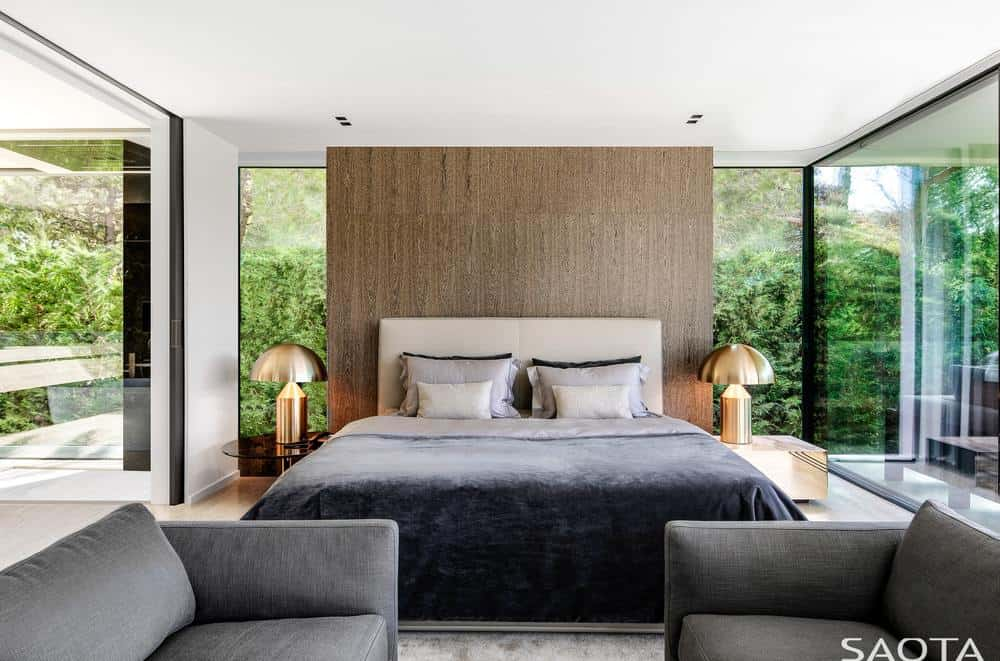 The highlight of this simple and bright Contemporary-style bedroom are the two golden table lamps flanking the light gray headboard of the bed that matches the hue of the cushioned armchairs at the sitting area by the foot of the bed. These are all illuminated by the large glass windows.