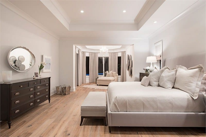 Minimalist living room with stark white walls, elegant tray ceilings, and a bow window dressed in gray draperies. The natural hardwood flooring provides warmth and comfort to the room.