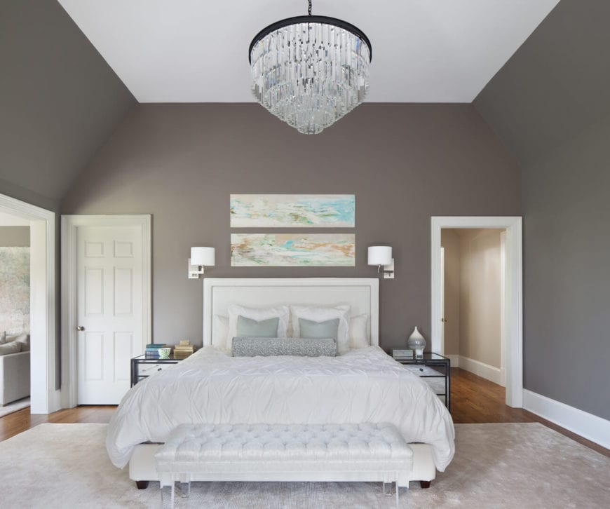 The brilliant decorative crystal pendant light hanging from the white ceiling stands out against the gray walls. These are adorned with a couple of colorful abstract paintings mounted over the white cushioned headboard of the traditional bed with a matching white cushioned bench at the foot.
