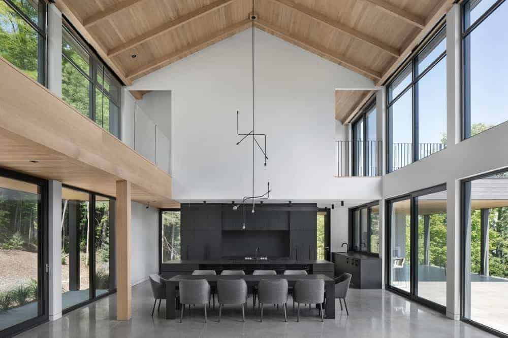 This is a Contemporary-style kitchen that is within a great room that also houses the dining area. It has a high ceiling with a wooden cathedral finish and hangs a peculiar chandelier over the area. The kitchen is mostly made of black cabinetry paired with a black wall that makes it stand out against the brightness of the great room.