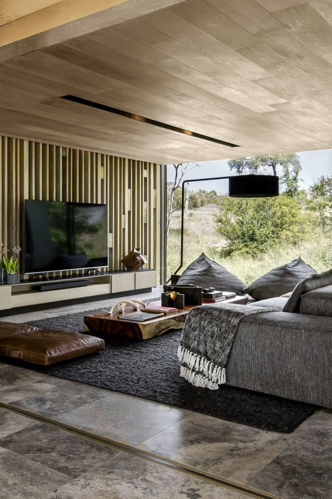 This is a charming and bright Contemporary-style living room brightened by the large glass wall that showcases the green landscape outside. This brings a dash of color to the gray sofa, area rug and flooring that are paired with a wooden ceiling, wooden wall behind the TV and the rustic wooden coffee table.