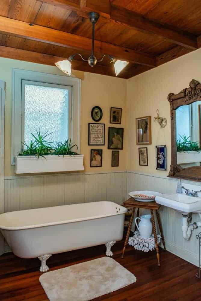 Cottage style bathroom decorated with gallery frames mounted on the yellow walls and a wood carved mirror above a wash basin. It has a clawfoot tub paired with a wooden side table and beige rug.