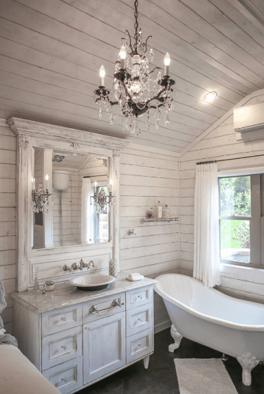 Cottage style bathroom with distressed shiplap walls and vaulted ceiling. It includes a soaking tub and a white vessel sink vanity with mirror lighted by vintage crystal sconces and matching chandelier.