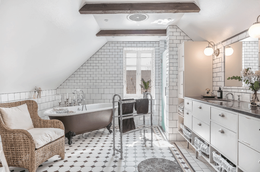 This bathroom features white brick walls and vaulted ceiling lined with natural wood beams. It has a brown clawfoot tub surrounded by a rattan chair and freestanding towel rack.