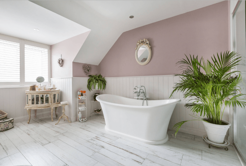 Charming bathroom accented with indoor plants that create tropical vibes. It has a pale pastel pink walls and distressed white wood plank flooring.