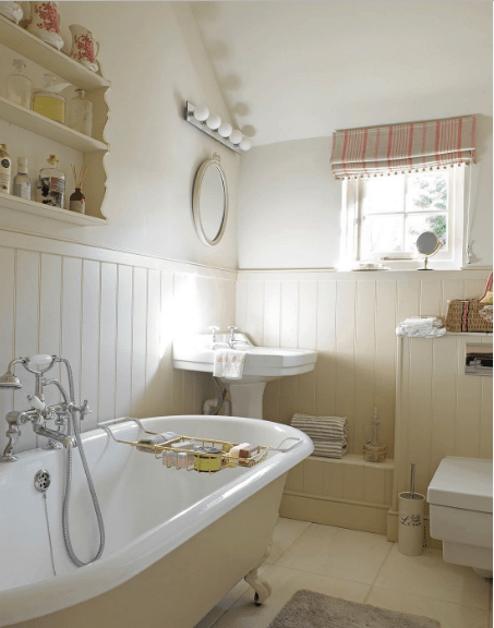 The cream bathroom boasts a beige bathtub fitted with chrome fixtures along with a pedestal sink paired with a mirror mounted above the bedboard wall.