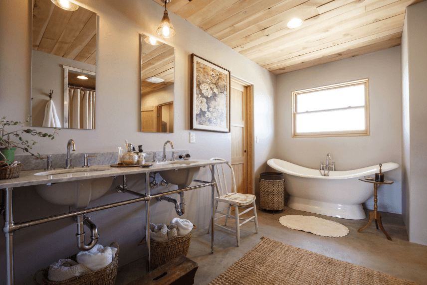 Warm bathroom showcasing dual sink washstands with frameless mirrors illuminated by pendant lights. It has concrete flooring topped with a woven rug.