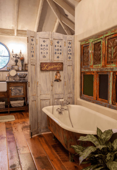 Shabby chic style bathroom offers a freestanding bathtub that complements with the artworks mounted on the white wall.
