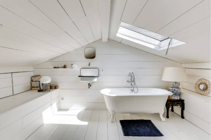 White bathroom covered with shiplap walls and floors along with a cathedral ceiling fitted with a skylight. It has a clawfoot tub with a wooden table on the side topped with a desk lamp.