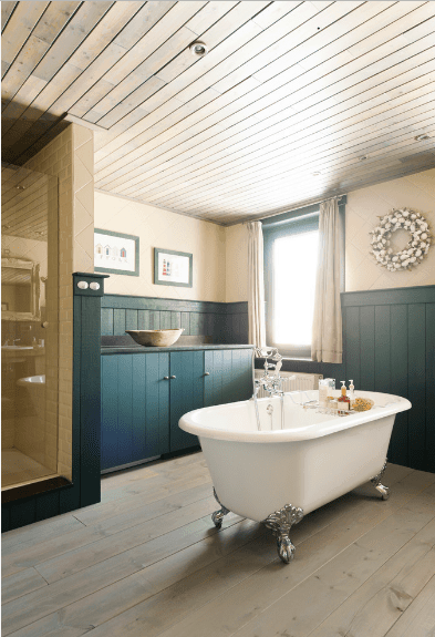 Shabby chic bathroom boasts a clawfoot bathtub facing the teal vessel sink vanity that matches with the beadboard wall. It has a natural wood plank flooring and ceiling.