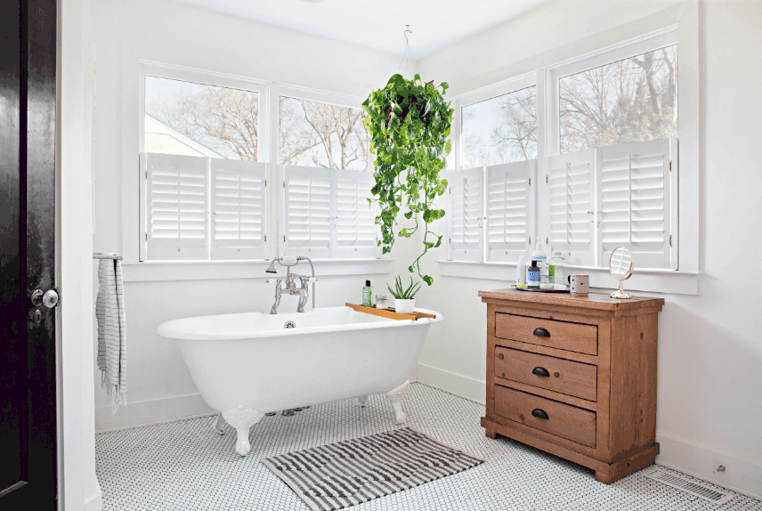 Fresh bathroom surrounded with glass windows wrapped in white shutters. It includes a freestanding bathtub accompanied by a wooden chest drawer.