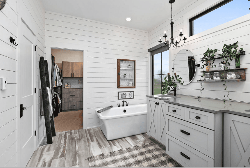 Airy bathroom features a soaking tub and dual sink vanity with gray granite countertop and a round mirror. It has a black ladder against white shiplap wall that serves as a towel rack.
