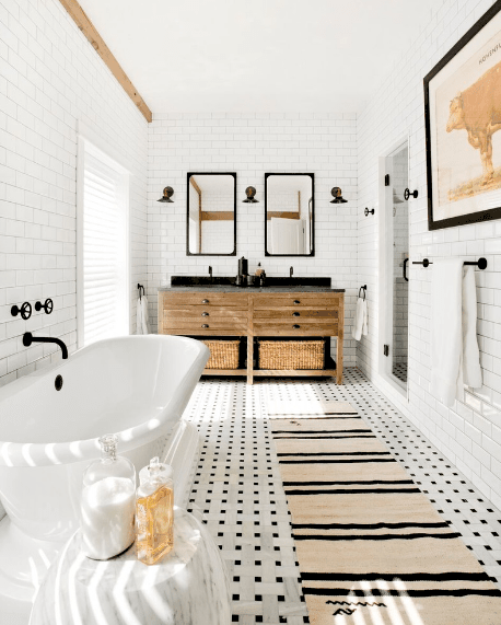 Gorgeous bathroom with white subway tiled walls and black and white patterned floor topped with a beige striped runner.
