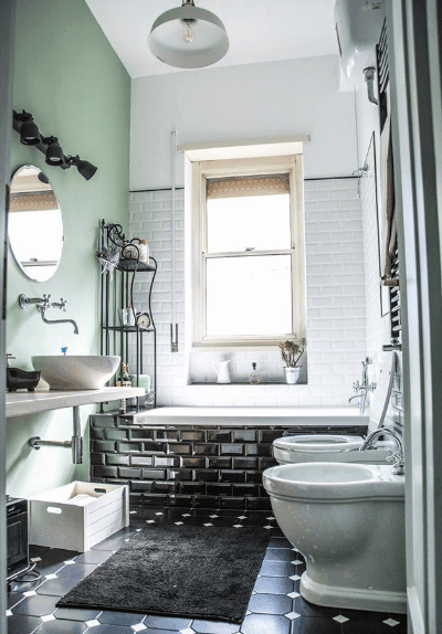 Marvelous bathroom features a soaking tub with high gloss black brick surround tiles. It includes a pair of toilets and a floating vessel sink vanity.