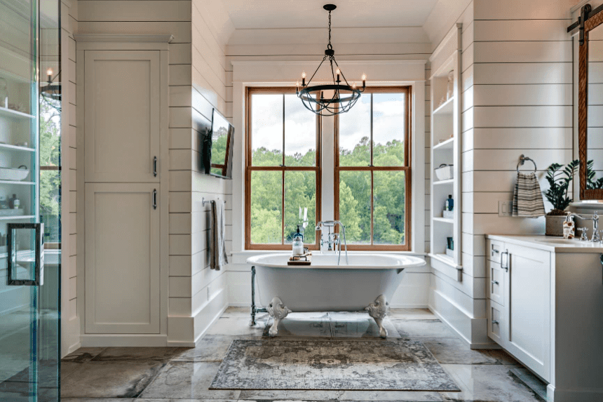 Cottage style bathroom illuminated by a wrought iron chandelier that hung over a clawfoot tub placed beneath the wooden framed window.