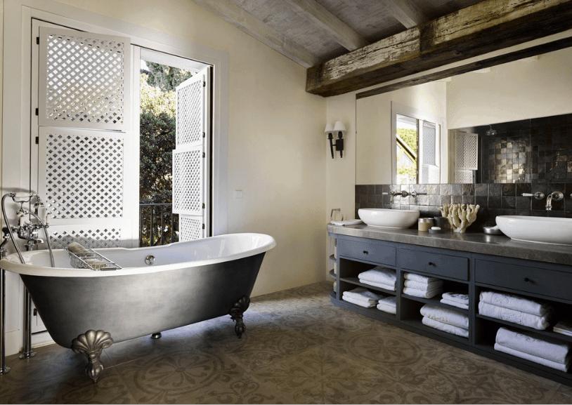 Dark bathroom offers a dual vessel sink vanity with dark gray tiled backsplash and a black clawfoot tub over a vintage patterned floor.
