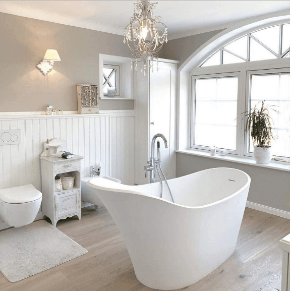 A crystal chandelier illuminates the freestanding bathtub in this bright bathroom along with natural light that flows through the arched glass window.