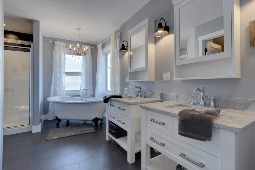 The elegant bathroom showcases two white vanities with marble countertops and medicine cabinets along with a clawfoot bathtub placed beneath glass windows wrapped in white sheer curtains.