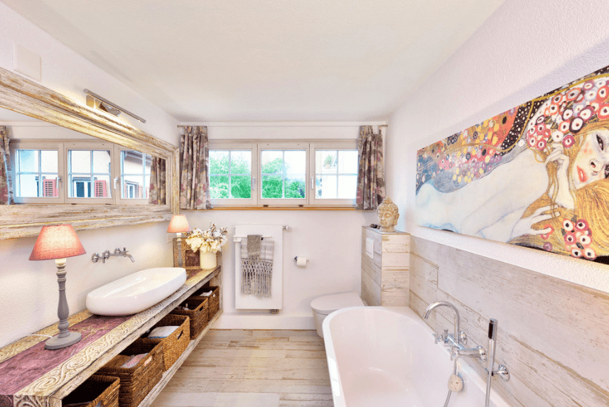 Fabulous bathroom decorated with a huge rectangular artwork mounted above the bathtub. It has a vessel sink vanity paired with a lengthy mirror and lighted by pink table lamps and a wall sconce.