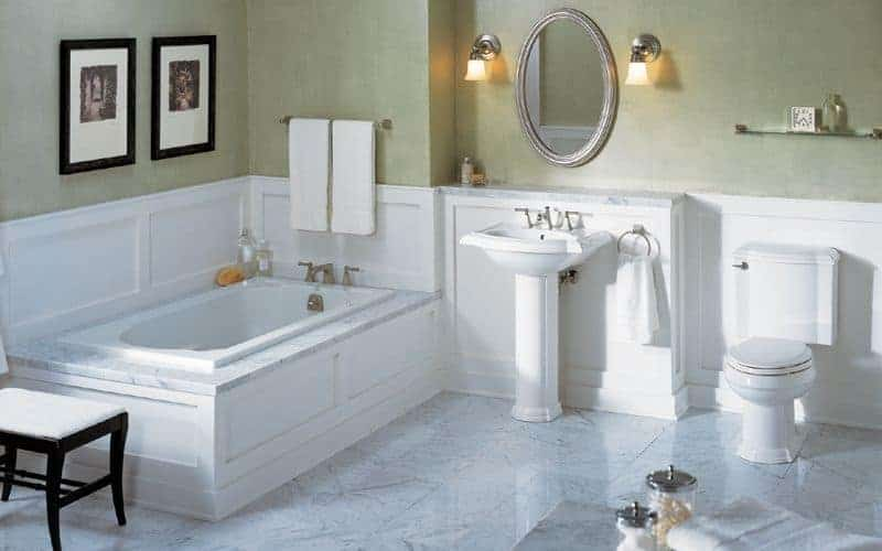 Bathroom with a toilet and bathtub topped with white marble that matches the tiled flooring. It also includes a pedestal sink placed in the middle with a mirror mounted above white wainscoting.