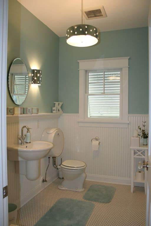 A matching dotted wall sconce and drum chandelier illuminate this cottage style bathroom. It has aqua walls over white beadboard wainscoting fitted with a single panel window.