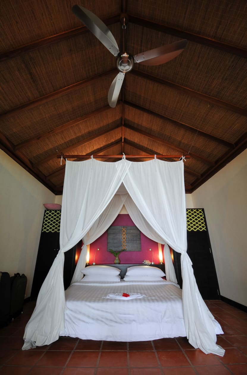 This bedroom offers a wooden canopy bed dressed in white bedding. It has a terracotta flooring and wooden cathedral ceiling.