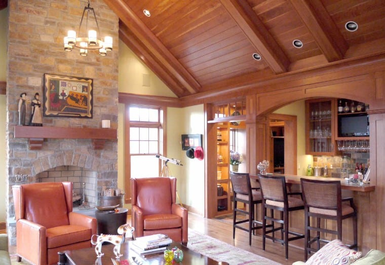 Living room with a bar boasts leather recliners that sit in front of the stone fireplace lined with a wood mantel and lighted by a wrought iron chandelier that hung from the wood plank cathedral ceiling.