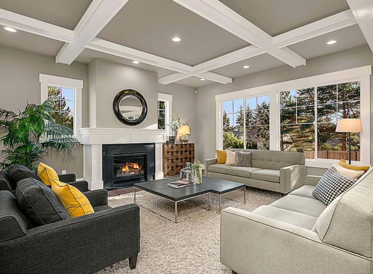 This is an elegant formal living room with white exposed beams at the gray ceiling that matches the light gray sofas and the fireplace with a white mantle. These are contrasted by the dark gray cushioned arm chairs as well as the dark coffee table.