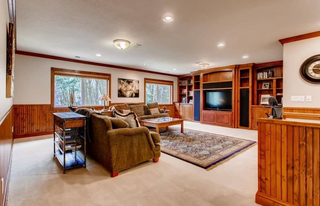 The beige carpeted floor is topped with a colorful patterned rug paired with a pair of inviting velvet sofas. The built-in cabinets that also serve as TV housing and shelves seem to blend into the glass windows and walls with its varnished wooden beauty.