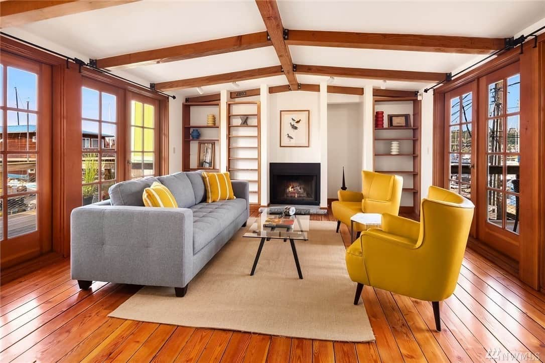 The stand-outs of this Craftsman-Style living room are the mustard yellow elements of the two leather single sofas and striped throw pillows on the long gray sofa. The wooden floors and arched ceiling with wooden exposed beams are complemented by a fireplace with a dark frame and French windows on either side of the room.