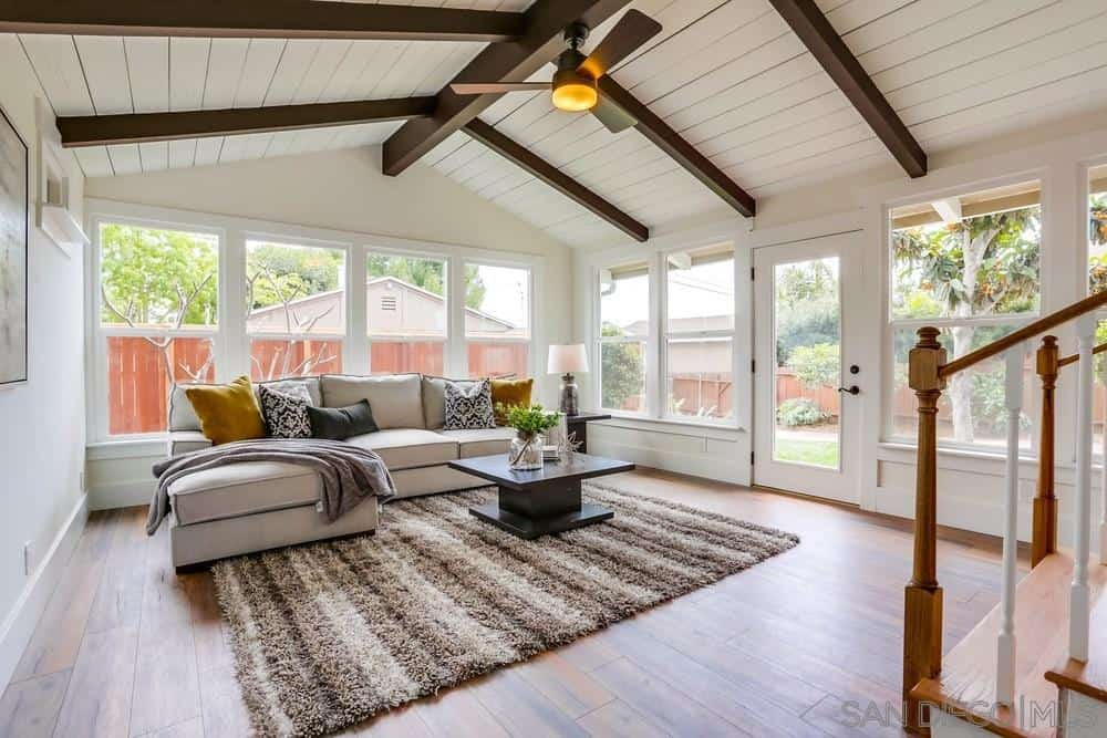 The white cathedral ceiling of this Craftsman-Style living room has wooden exposed beams that contrast the walls that are dominated by glass windows and door. A beautiful striped rug is placed over the wooden floor and paired with a massive L-shaped sofa.