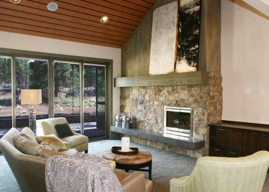 The fireplace that has metallic frames are inlaid into a rough stone wall that extends to the high ceiling and fitted with a couple of ledges that support artworks. Sliding glass doors make up one of the walls that bring natural light to the cushioned sofa chairs facing the fireplace.