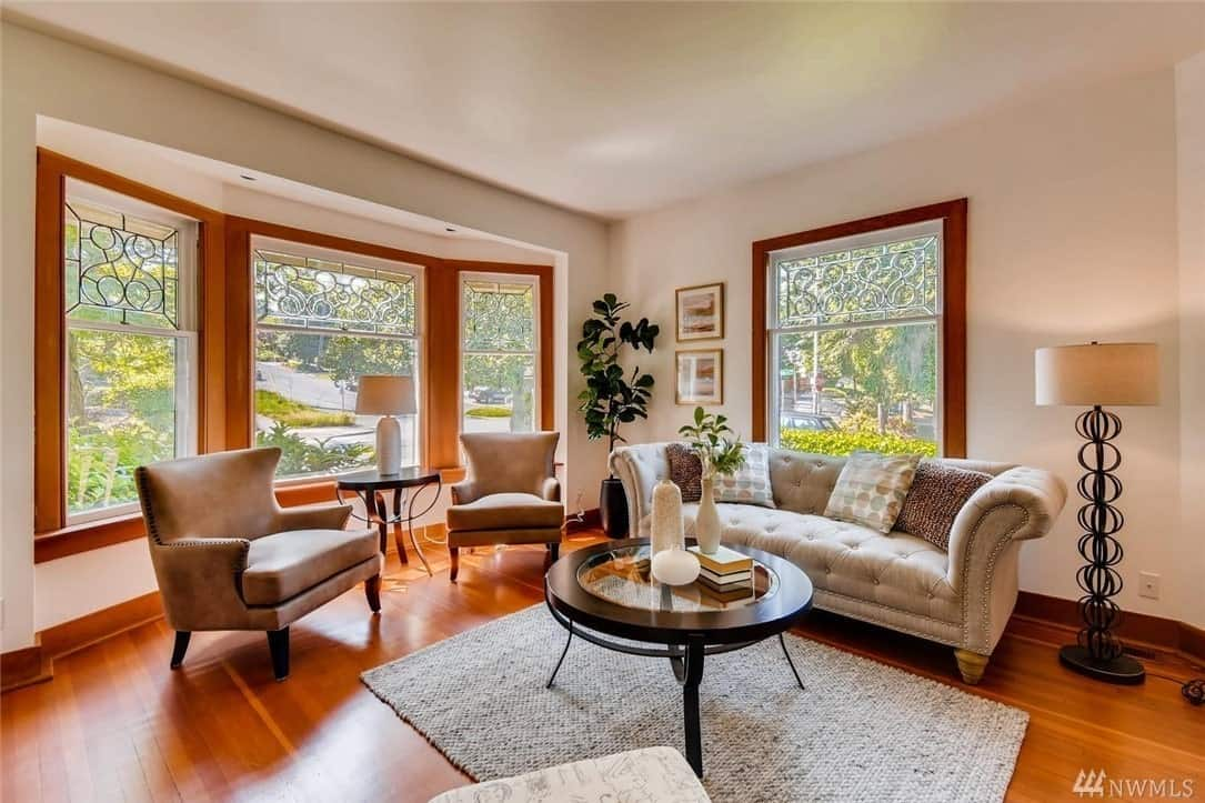This is an airy Craftsman-style living room with abundant natural lighting coming from its massive glass windows that surround the cushioned sofas. The hardwood flooring is topped with a woven area rug and dark wooden circular coffee table that goes well with the side table and wooden frames of the windows.