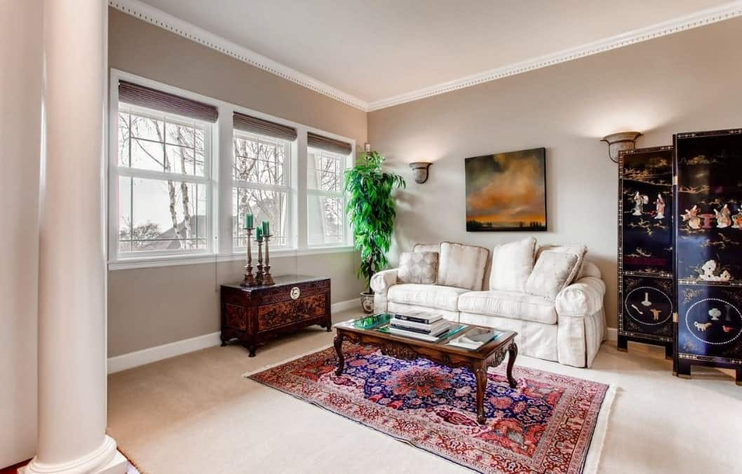 The colorful patterned area rug, foot locker and foldable decor stand out in this predominantly light-hued Craftsman-Style living room. The light gray walls are augmented by a couple of wall-mounted lamps and windows that provide natural light to the comfortable white sofa.