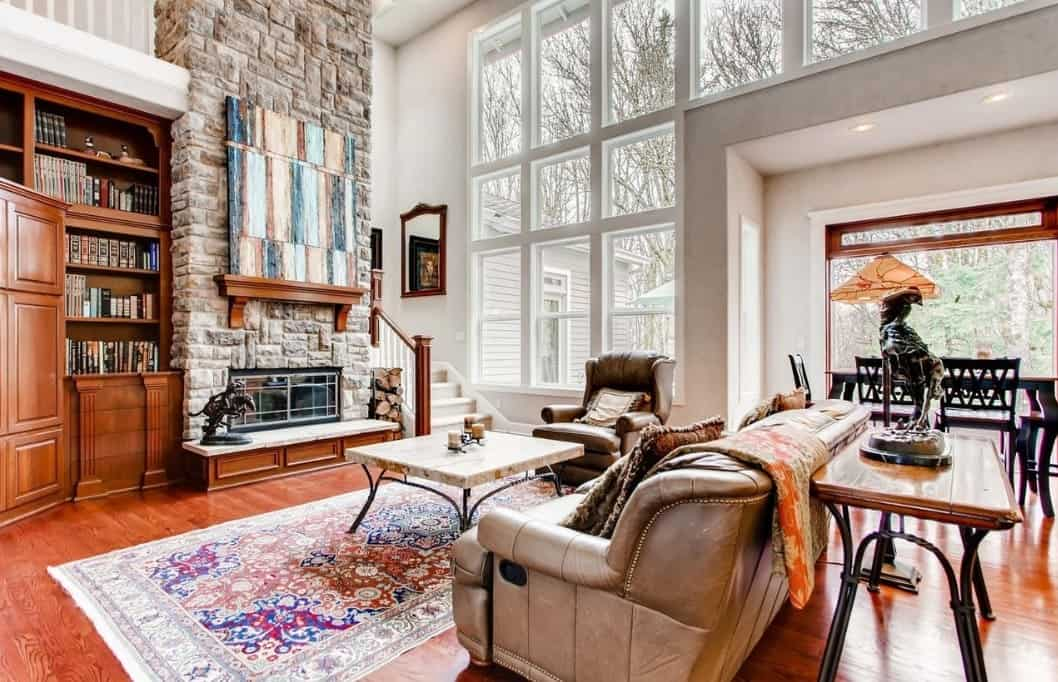 A massive gray stone chimney rises up from the small fireplace that brightened up by the floor-to-ceiling glass windows in this spacious Craftsman-Style living room. Above the fireplace, A colorful abstract painting is mounted which contrasts well with the wood floors, shelves and cabinets. The leather sofas are paired with a rectangular coffee table on a colorful patterned rug.