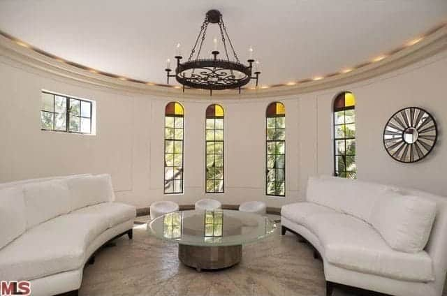 Identical white sofas with a glass top table illuminated by a wrought iron chandelier surround this circular living room.