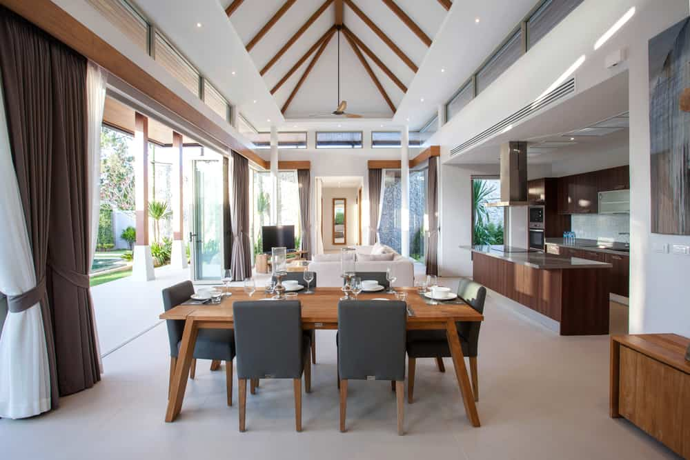 An airy open floor plan house features bi-fold doors covered with white and brown draperies along with a cathedral ceiling fitted with recessed lighting.