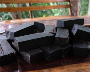 Cut blocks of ebony wood on a wooden table.