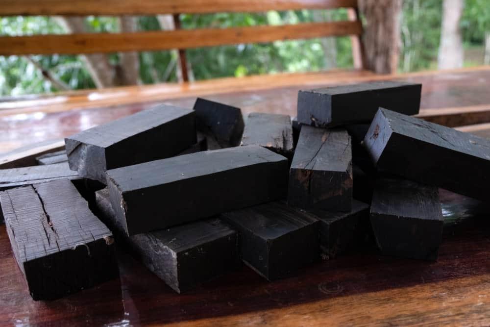 Cut blocks of ebony wood on a wooden table.