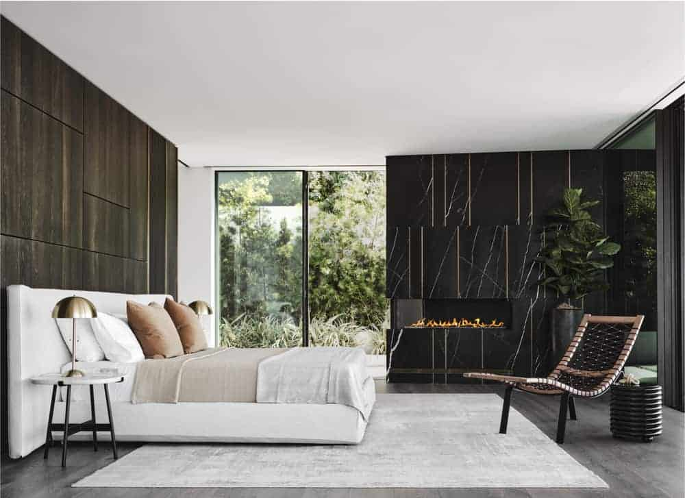 The primary bedroom of the house has a large white cushioned bed paired with white bedside tables. These are then contrasted by the large black marble wall that houses the modern fireplace on the far corner adorned with a potted plant.