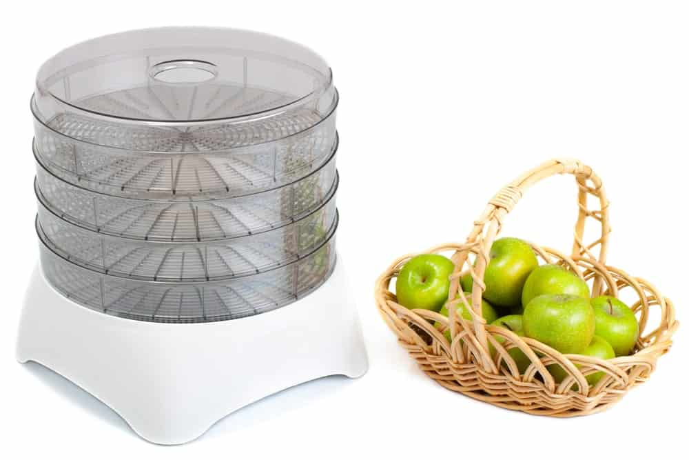 An empty food dehydrator beside a basket of green apples.