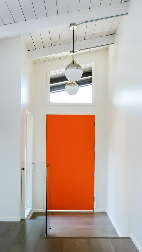 A bright orange door below a glass window stands out in this entryway. It has a white shiplap vaulted ceiling with exposed wood beams and hanging globe pendant lights.