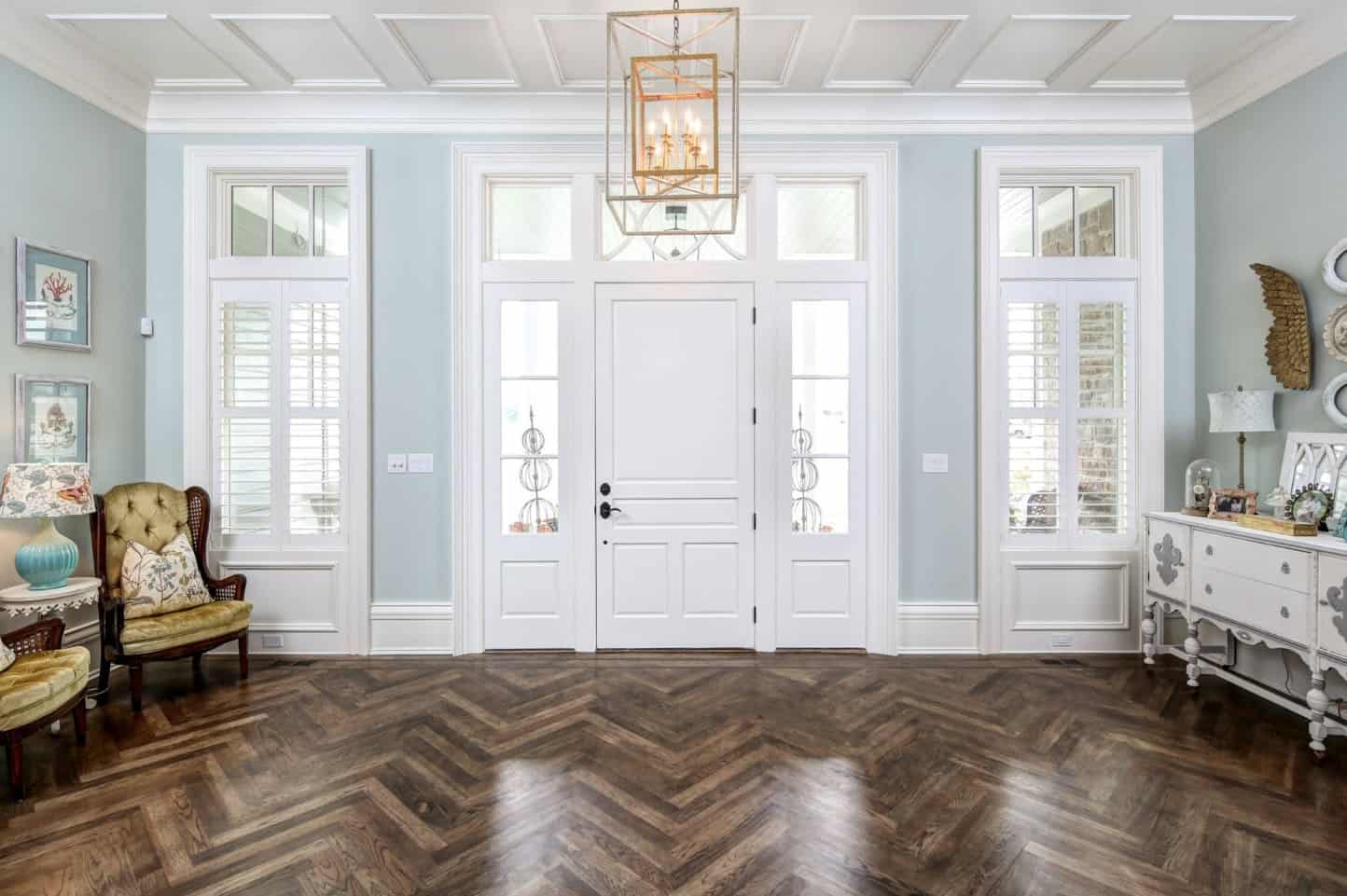 Charming foyer illuminated by a brass caged pendant that hung from a coffered ceiling and over a herringbone wood flooring.