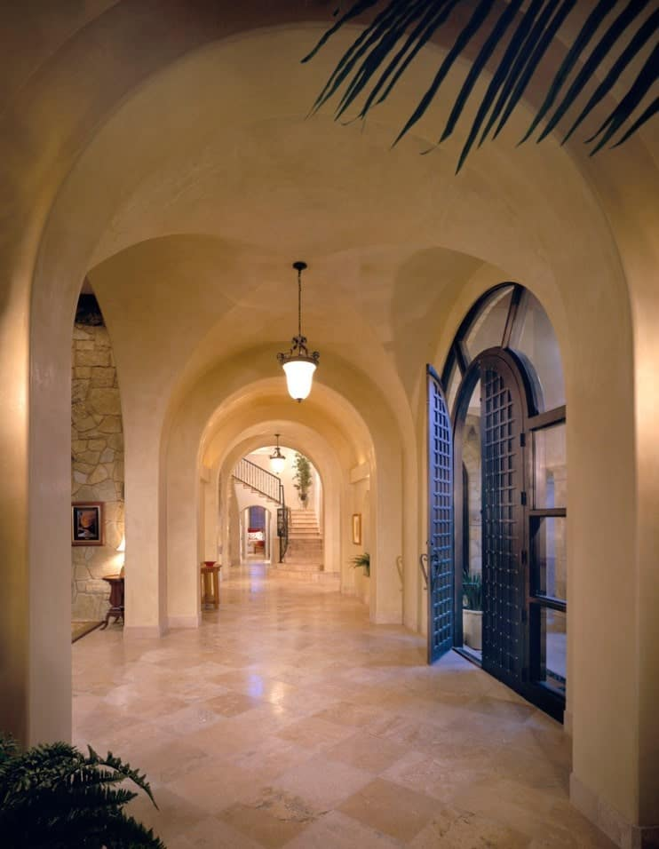 Mediterranean hallway framed with series of arches lighted by vintage pendants. It boasts a black metal entry door with surround glass panels.