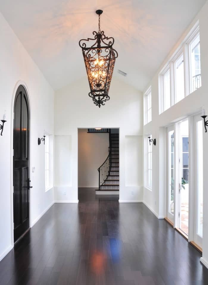 White foyer features a dark wood plank flooring and cathedral ceiling with a hanging ornate wrought iron pendant.