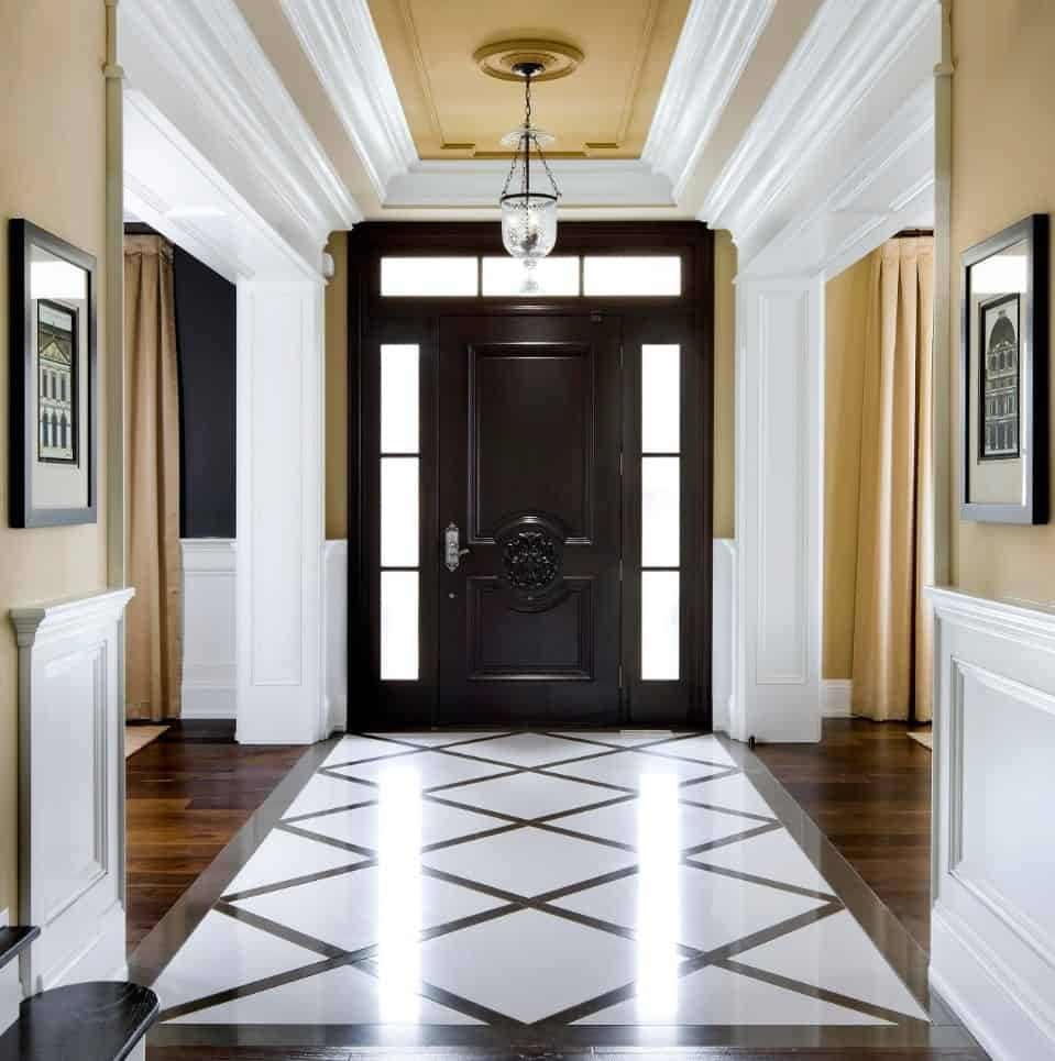 Marvelous entryway with a black front door surrounded by frosted glass panels fixed to the mustard wall that's clad with white crown molding and wainscoting.