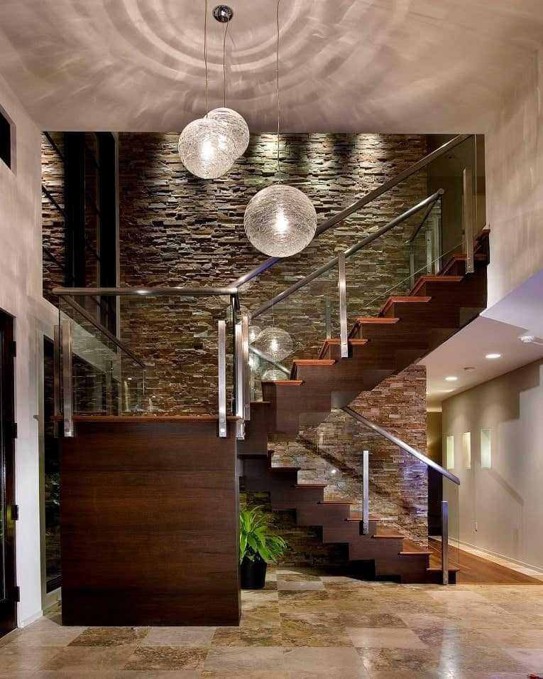Huge ball pendants illuminate this luxurious foyer with wooden half-turn staircase framed with glass railing and fixed to the stone accent wall.