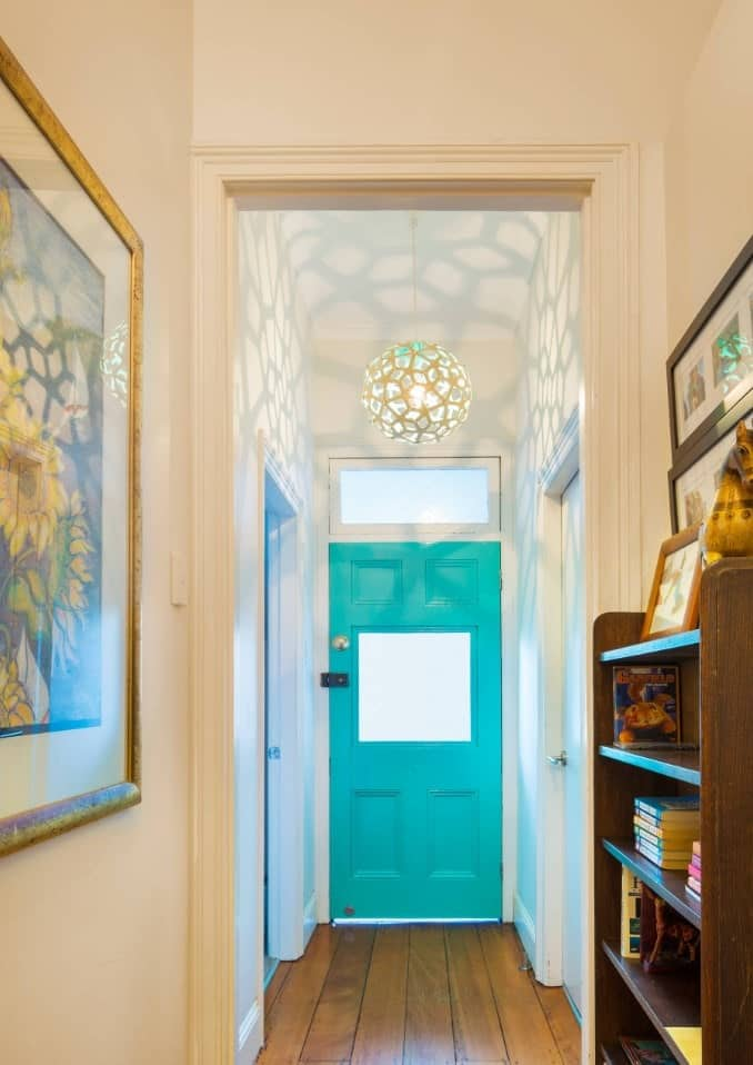 Beach style foyer boasts an aqua entry door and lovely ball pendant along with natural wood plank flooring.