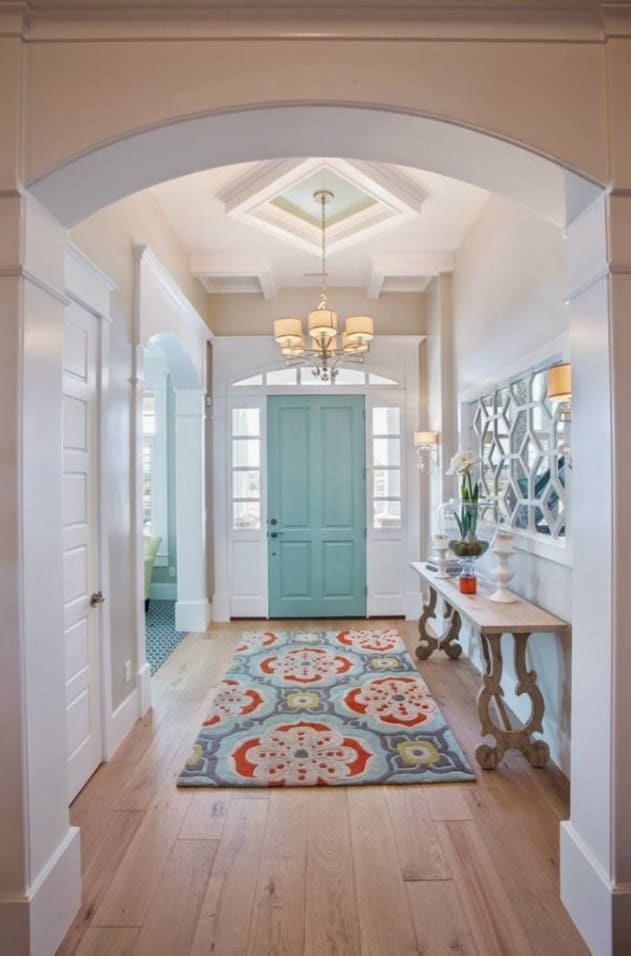 White foyer accented with a turquoise door and floral rug that lays on a light wood plank flooring. It is lighted by a lovely pendant that hung from the tray ceiling.