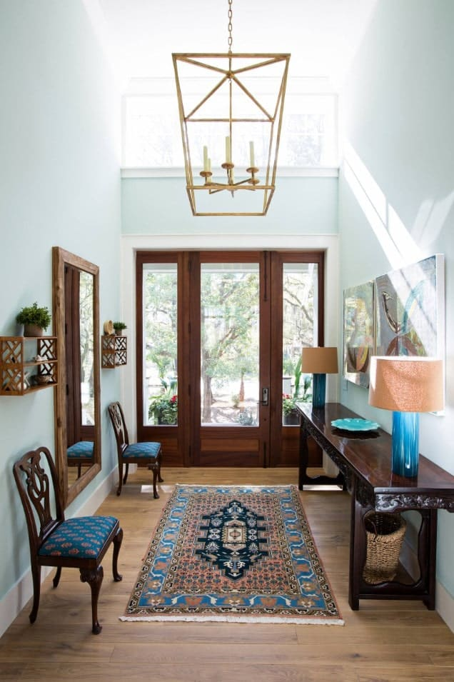 Blue foyer incorporated with wood furniture and flooring. It is illuminated by a caged pendant along with natural light from the glazed door.